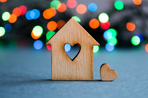 Wooden house with hole in the form of heart with little heart on colorful bokeh background.
